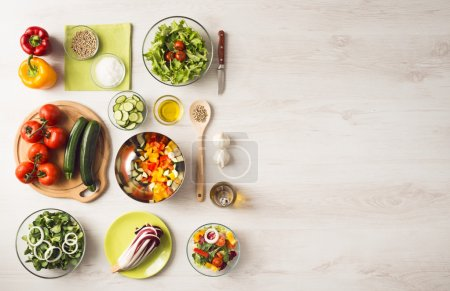 Photo for Healthy eating concept with fresh vegetables and salad bowls on kitchen wooden worktop, copy space at right, top view - Royalty Free Image