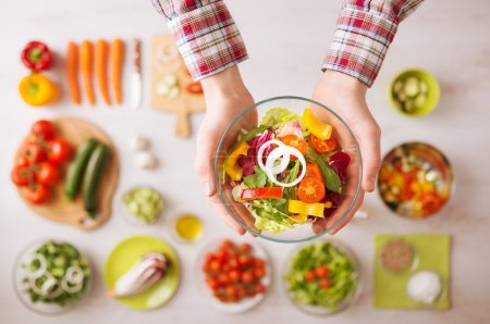 Photo for Man holding a fresh garden salad bowl with raw sliced vegetables, hands close up top view, ingredients and utensils on background - Royalty Free Image