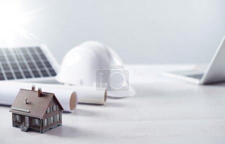 Foto de Escritorio de ingeniería estructural y arquitecto con casco de seguridad, panel solar y casa modelo - Imagen libre de derechos