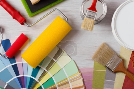 Photo for Painter and decorator work table with house project, color swatches, painting roller and paint brushes, top view - Royalty Free Image