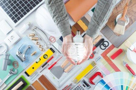 Foto de Las manos del hombre se cierran sosteniendo una lámpara de ahorro de energía CFL, herramientas de trabajo y reparación en el fondo, vista superior - Imagen libre de derechos