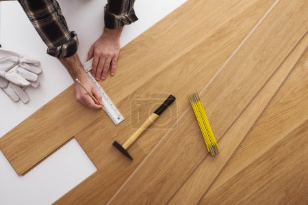 Photo for Carpenter installing a wooden flooring and measuring with a precision ruler, top view - Royalty Free Image