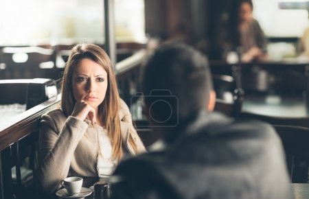 Photo for Friends at the bar, he is giving her bad news - Royalty Free Image