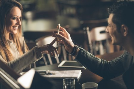 Photo pour Young fashionable couple at the bar using a mobile touch screen phone - image libre de droit