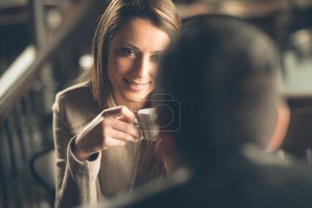 Photo pour Jeune couple à la mode sortir ensemble au bar, elle prend un café - image libre de droit