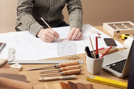 Photo for Professional architect and construction engineer working at office desk hands close-up, he is drawing on a building draft with a pencil and a ruler - Royalty Free Image