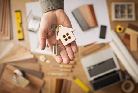 Photo for Real estate agent handing over a house key, desktop with tools, wood swatches and computer on background, top view - Royalty Free Image