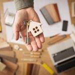Real estate agent handing over a house key, deskto...