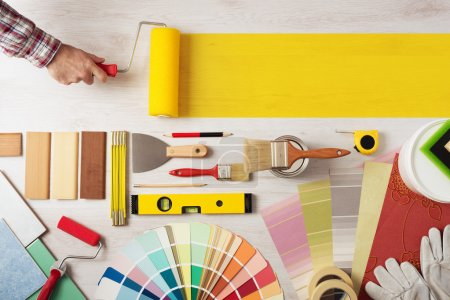 Photo for Decorator holding a painting roller and painting a wooden surface, work tools and swatches at bottom, banner with copy space - Royalty Free Image