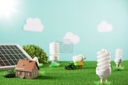 Photo for Environmental friendly toy town with model house, CFL lamps as trees and tractor carrying a light bulb - Royalty Free Image