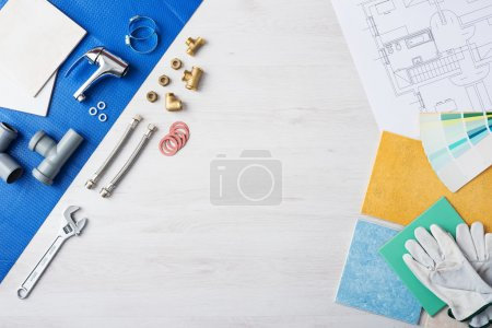 Photo for Plumber's work table banner with work tools, faucet, tiles and color swatches, top view, copy space at center - Royalty Free Image