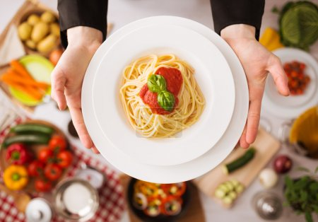 Photo for Professional chef's hands cooking pasta on a wooden worktop with vegetables, food ingredients and utensils, top view - Royalty Free Image