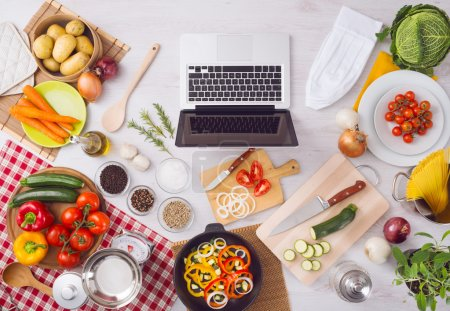 Photo for Home kitchen table top view with laptop, food ingredients, raw vegetables, kitchenware and utensils, top view - Royalty Free Image