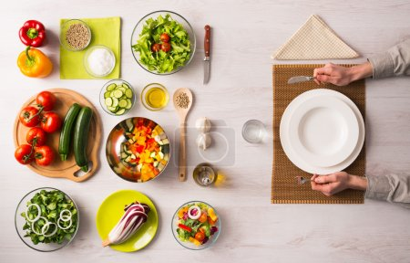 Photo for Healthy vegetarian meal concept with table set, hands holding fork and knife and fresh raw vegetables - Royalty Free Image