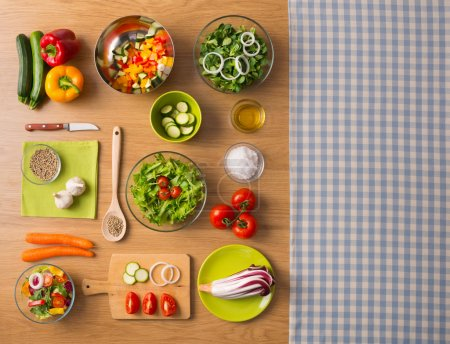 Photo for Healthy fresh vegetarian food on kitchen table with checked tablecloth on the right, top view - Royalty Free Image