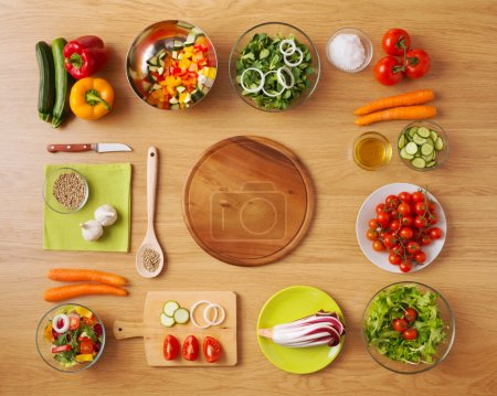 Photo for Creative vegetarian cooking at home concept with fresh healthy vegetables chopped, salads and kitchen wooden utensils, top view with copy space - Royalty Free Image