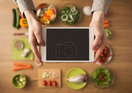 Photo for Hands holding a digital touch screen tablet with fresh vegetables and kitchen utensils on background, top view - Royalty Free Image