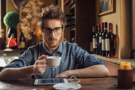 Photo pour Guy de hipster nerd à lunettes, assis au bar table et en utilisant une tablette - image libre de droit
