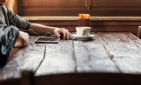 Photo pour Young man having a coffee break at the bar and listening to music with his tablet using earphones - image libre de droit