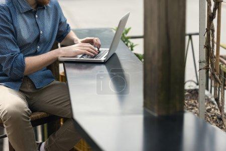 Photo pour Homme méconnaissable à l'aide d'un ordinateur portable modern sur une table extérieure, rue sur fond - image libre de droit