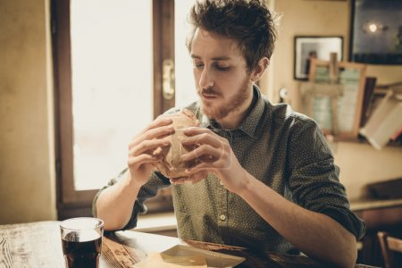 Photo for Young man having a lunch break with a tasty ham sandwich and a glass of coke - Royalty Free Image