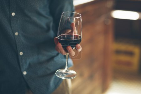 Photo for Young man holding a glass with red wine, bar on background - Royalty Free Image