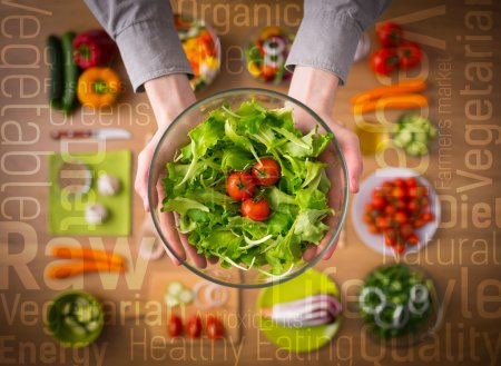 Photo for Hands holding an healthy fresh vegetarian salad in a bowl, fresh raw vegetables on background and healthy eating text concepts - Royalty Free Image