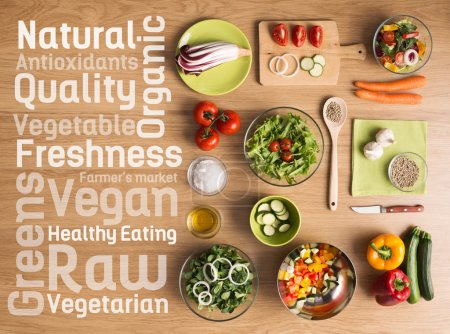 Photo for Creative vegetarian cooking at home with fresh healthy vegetables chopped, salads and kitchen wooden utensils, healthy eating text concepts on the left - Royalty Free Image