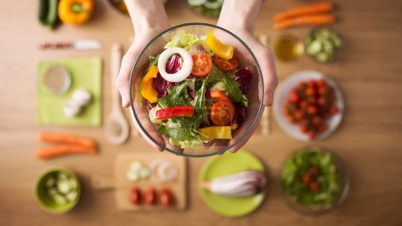 Photo for Hands holding an healthy fresh vegetarian salad in a bowl, fresh raw vegetables on background, top view - Royalty Free Image
