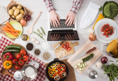 Photo for Man searching for recipes online using a laptop hands close up, kitchen tools and food ingredients all around, top view - Royalty Free Image