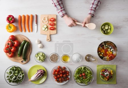 Photo for Man hands cooking at home holding a wooden spoon, fresh vegetables and food ingredients all around, top view - Royalty Free Image