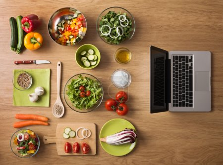 Photo for Online recipes concept with fresh vegetables, food ingredients and laptop on the right, top view - Royalty Free Image