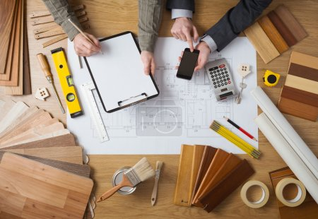 Photo for Business people working together on a building project, desktop top view with tools, wood swatches, mobile phone and blueprint - Royalty Free Image