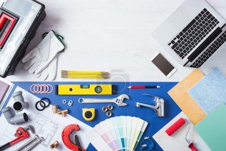 Photo pour Ordinateur portable sur une table en bois à côté des outils de travail de plomberie, tuiles, robinet et échantillons de couleur vue du dessus, concept de services de plomberie en ligne - image libre de droit