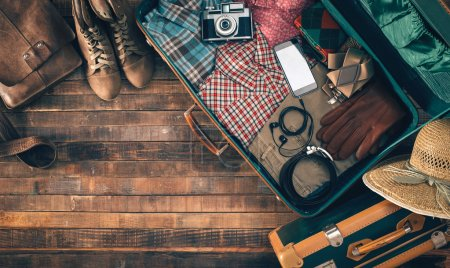 Photo for Vintage hipster suitcase packing before leaving with old suitcase, camera and accessories on a wooden table, top view - Royalty Free Image