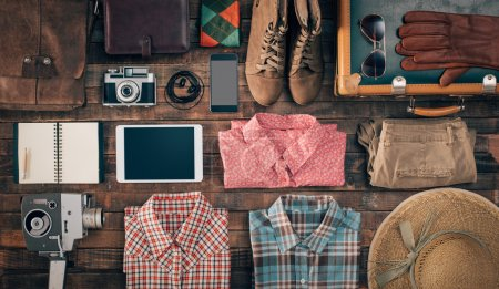 Photo for Hipster vintage accessories and clothing on a wooden table before packing, travel and vacations concept, top view - Royalty Free Image