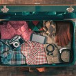 Vintage hipster traveler packing, open suitcase on...