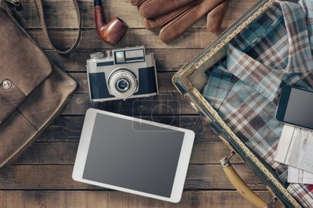 Foto de Vintage hipster traveler packing ready to leave with camera and digital touch screen tablet, top view - Imagen libre de derechos