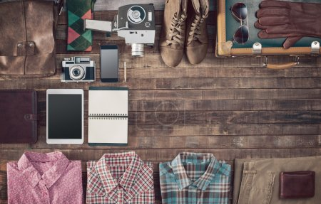 Foto de Vintage hipster suitcase packing before leaving with old suitcase, camera, tablet, clothing and accessories on a wooden table, top view - Imagen libre de derechos