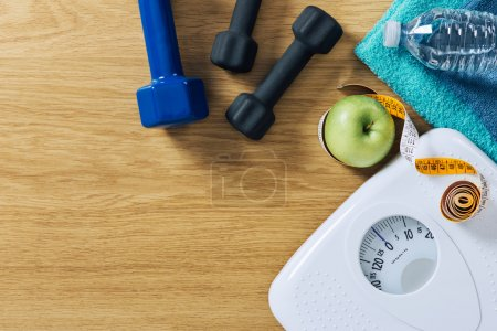 Photo for Fitness and weight loss concept, dumbbells, tape measure, white scale towels and water bottle on a wooden table, top view - Royalty Free Image
