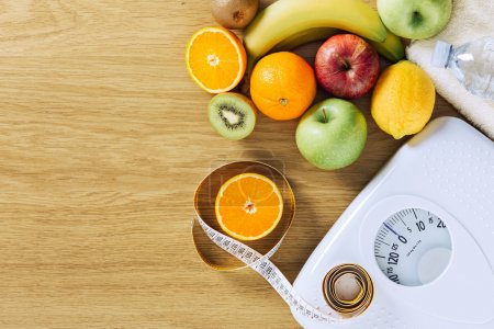 Photo for Healthy eating, fitness and weight loss concept, tape measure, white scale and fruit on a wooden table, blank copy space - Royalty Free Image