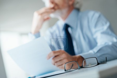 Photo for Pensive businessman with hand on chin looking away and holding a document, selective focus, glasses on foreground - Royalty Free Image