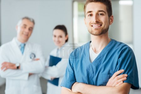 Photo for Young doctor posing and smiling at camera and professional medical staff on background, selective focus - Royalty Free Image