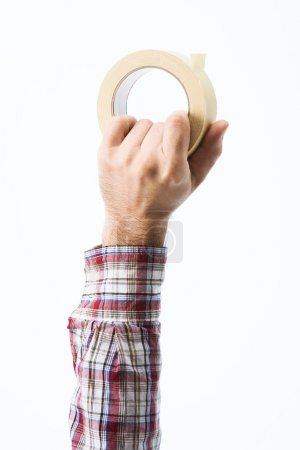 Hand holding a roll of masking tape