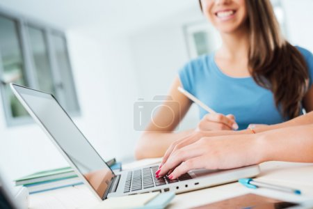 Photo for Girls sitting at desk and using a laptop, they are studying and social networking - Royalty Free Image