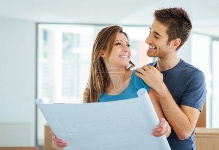 Photo pour Jeune couple heureux tenant un projet et planifiant leur nouvelle maison, déménagement et concept de rénovation - image libre de droit