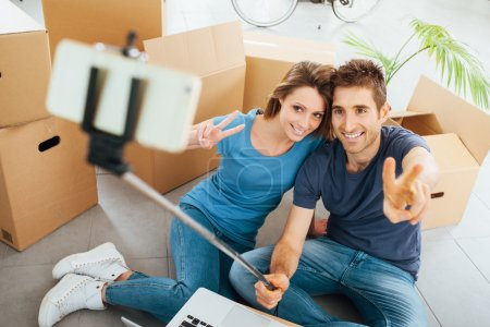 Photo for Smiling young couple sitting on their new house floor surrounded by cardboard boxes and taking selfies using a selfie stick - Royalty Free Image