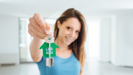 Photo for Beautiful smiling woman holding house keys of her new house, real estate and relocation concept - Royalty Free Image