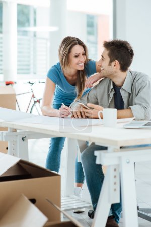 Photo for Romantic loving couple planning and designing their new house, they are staring at each other's eyes - Royalty Free Image