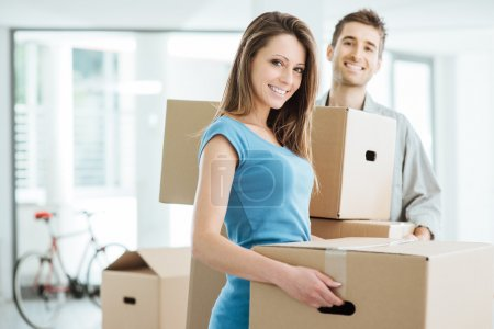 Photo for Happy smiling couple moving in a new house and carrying carton boxes, relocation and renovation concept - Royalty Free Image
